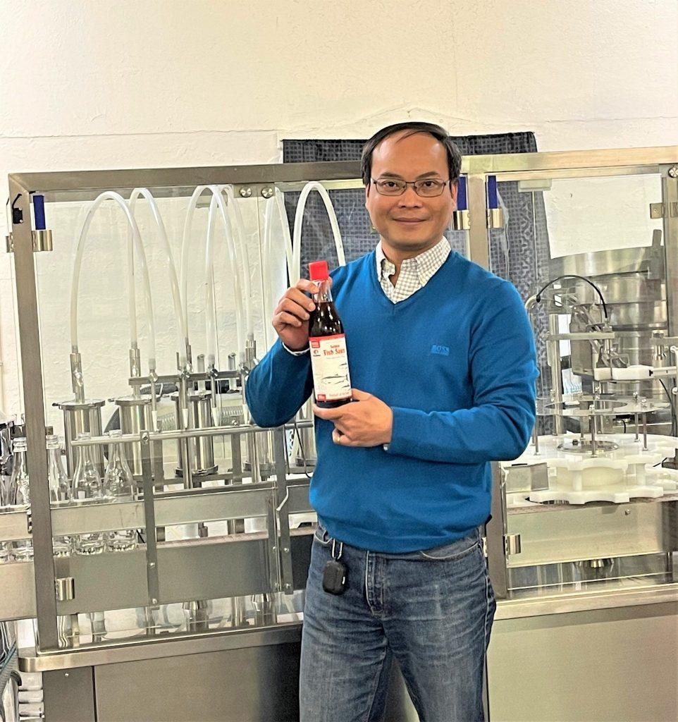 Trung Van Nguyen hos Noumami viser stolt frem en flaske med fermentert fiskesaus, med etiketter fra Skipnes.